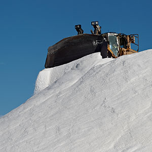 A loader adding salt to a drying pile.